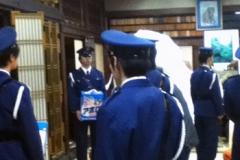 お寺の中に立ち尽くす警官
